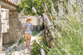 Rear view of beautiful blonde young female traveler wearing straw sun hat sightseeing and enjoying summer vacation in an old traditional costal town at Adriatic cost, Croatia