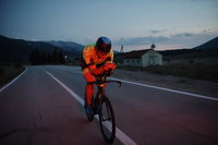 triathlon athlete riding bike at night