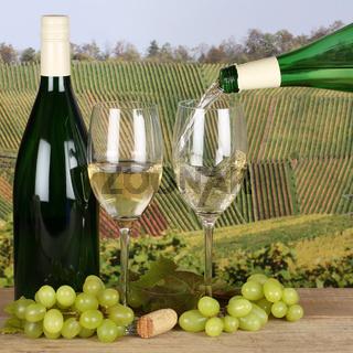 Weißwein aus einer Weinflasche in den Weinbergen in ein Glas eingießen