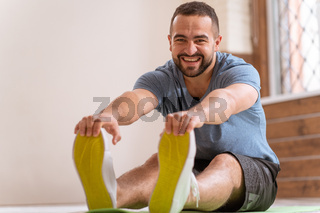 Young happy smiling fitness man doing stretching exercises at home. Amateur sports man in workout activity sitting on pad and stretch leaning to his toes. Hardworking guy exercising in apartment