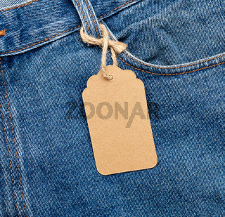 blank brown rectangular tag tied in the back pocket of blue folded jeans