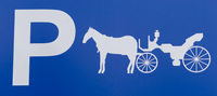 close up detail of a parking lot sign exclusively reserved for horse and carriage