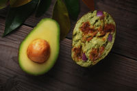 An Avocado cut in half on a wood surface with leaves. One half shows the seed while the other if fil