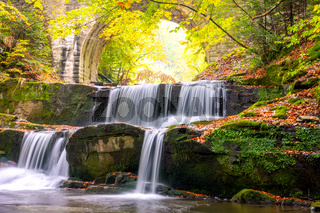 River Waterfall and Arch of a Stone Bridge in the Forest