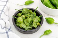 Cooked Padron peppers in a a bowl on marble table