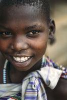 TOPOSA TRIBE, SOUTH SUDAN - MARCH 12, 2020: Girl in colorful garment with beads smiling and looking at camera in village of Toposa Tribe in South Sudan, Africa