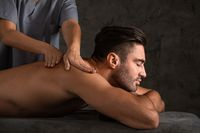 Man getting back massage at spa