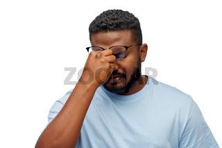 tired african man in lasses touching nose bridge
