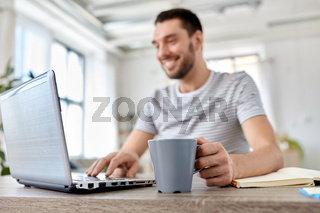 happy man with laptop drinking coffee at home