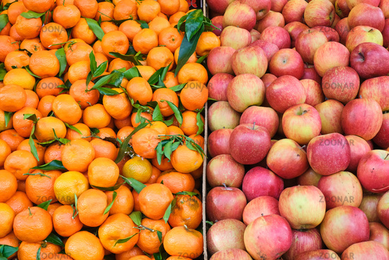 Tangerines and apples for sale at a market