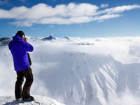 Skier at top of mount and snowy mountains in fog