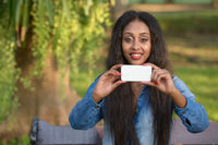 Happy young beautiful African woman taking picture with phone at the park