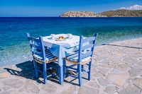 Plaka Lassithi with is traditional blue table and chairs and the beach in Crete Greece