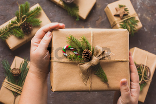 Female hands hold gifts in craft paper