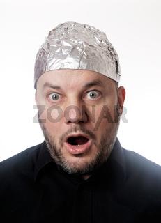 paranoid man wearing tin foil hat in shock