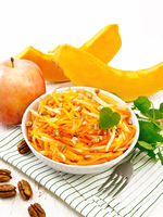 Salad of pumpkin and apple with nuts in bowl on board