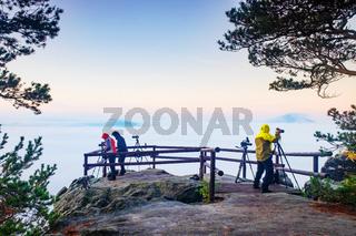 Working photographers within sunrise in autumn misty land