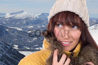Junge Frau schaut in den Bergen im Winter nach oben