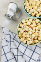 High angle shot of two different colored bowls of fresh popped popcorn with towl and salt shaker with salt spilling out. Vertical format.