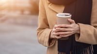 Close up on woman's hands holding a cup of coffee wearing beige coat on the street female fashion. Portrait of stylish young woman wearing autumn coat and red beret outdoors. Autumn accessories