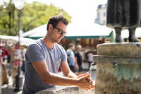 Young casual cucasian man washing hands with water from public city fountain on a hot summer day