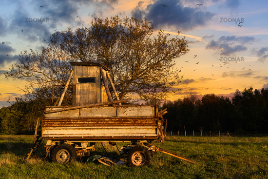 old trailer with high seat in the sunset