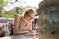 Thirsty young casual cucasian woman wearing medical face mask drinking water from public city fountain on a hot summer day. New social norms during covid epidemic