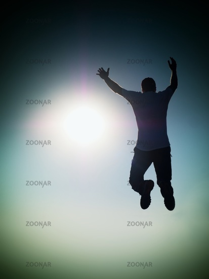 Man fly in air. Blue  Toned effect. Man falling down with raised arms. Sun and colorful sky backgrou