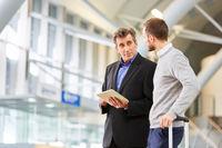 Zwei Geschäftsleute mit Tablet am Flughafen