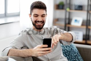 man in earphones listening to music on smartphone