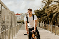 Handsome guy in casual clothes is cycling in he evening city. Outdoor.