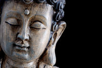 Face of a wooden Buddha sculpture isolated on black background
