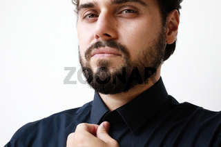 Close-up of handsome young man with beard in blue shirt looking with serious expression in camera.