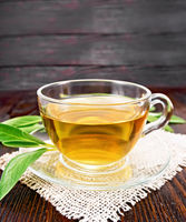 Tea herbal with sage in glass cup on wooden board