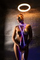 Sexy woman with neon light stripe in studio