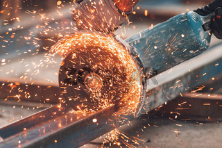 Construction worker using Angle Grinder cutting Metal at construction site.