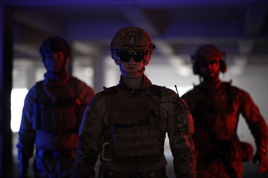 soldier squad team walking in urban environment colored lightis