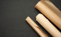 rolls of brown parchment paper on a wooden background