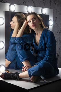 Pensive woman dressed in denim overalls
