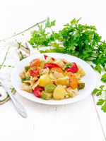 Ragout vegetable with zucchini on white wooden board