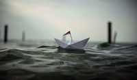 Paper boat in big waves