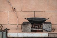 Old black metal pan wok on a gas cooker