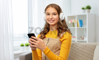teenage girl in headphones with smartphone at home