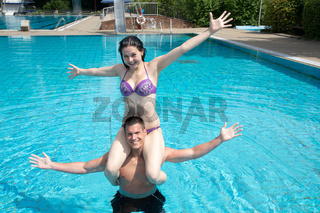 Girl sitting on man's shoulders at swimming pool