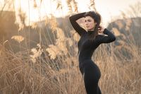Sexy woman doing stretching and physical activity, sunrise, wheat and nature, meditation, yoga