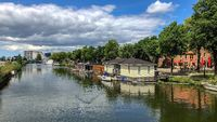 canal in amsterdam with houseboats and a blue sky