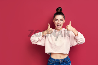 Happy smiling hipster woman showing thumbs up on pink background