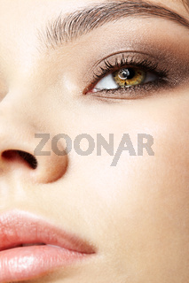 Closeup macro portrait of female face with pink lips and smoky eyes beauty makeup.