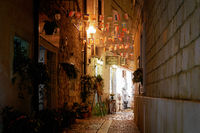Shops in a narrow alley in the port city of Porec in Croatia in the evening