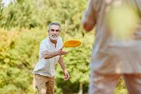 Paar Senioren beim Frisbee spielen